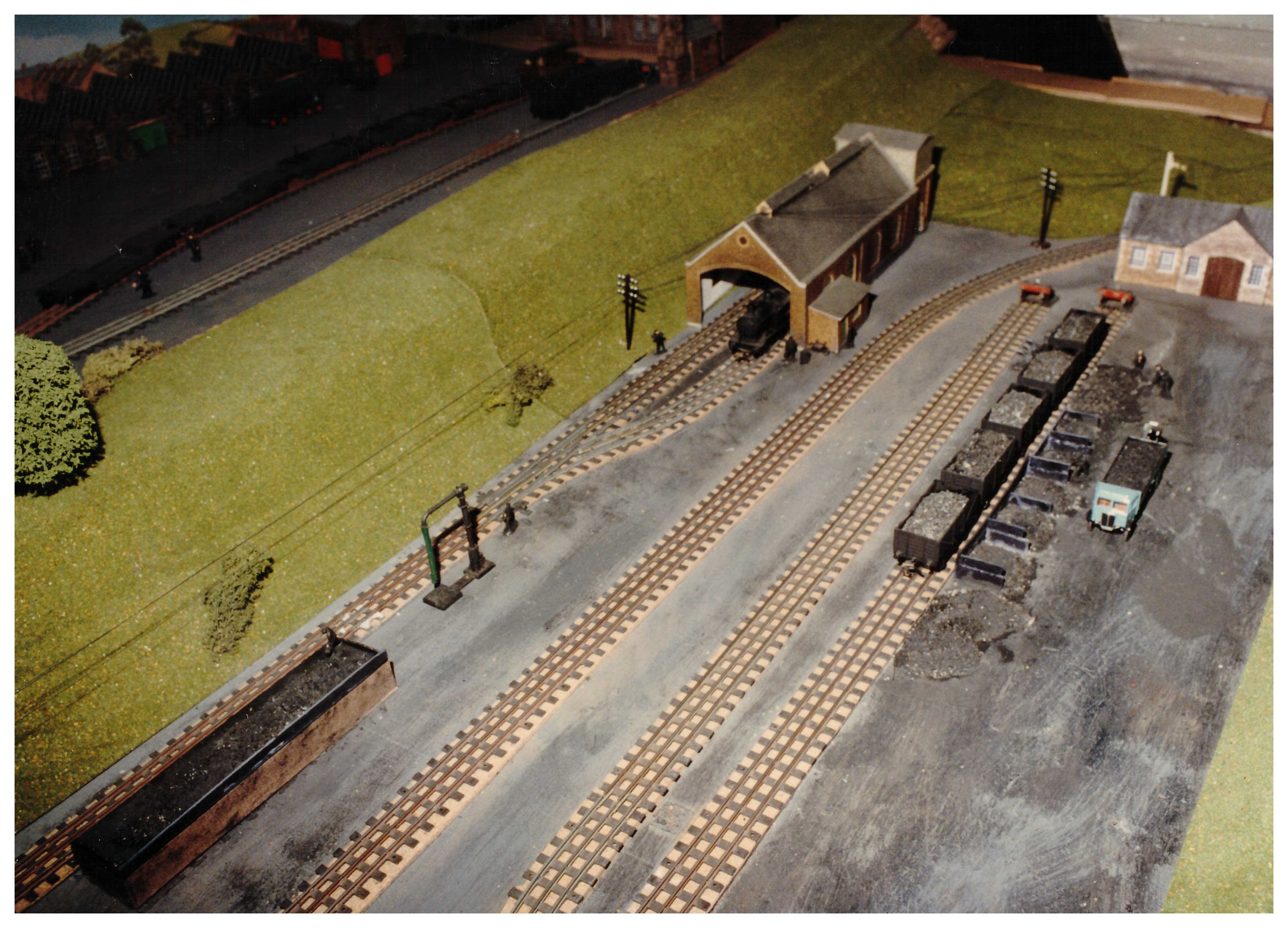 Engine shed with mainline disappearing into the distance